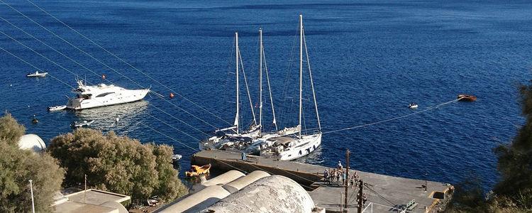 Яхты у пирса деревни Ия на острове Санторин. Киклады. Греция